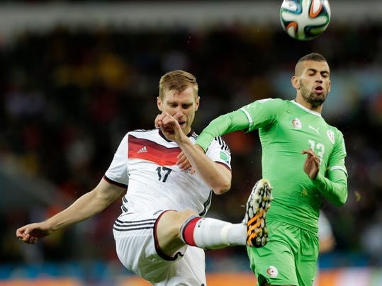 Germany's Per Mertesacker, left, clears the ball in front of Algeria's Islam Slimani during the World Cup round of 16 soccer match between Germany and Algeria at the Estadio Beira-Rio in Porto Alegre, Brazil, Monday, June 30, 2014. (AP Photo/Matthias Schrader)