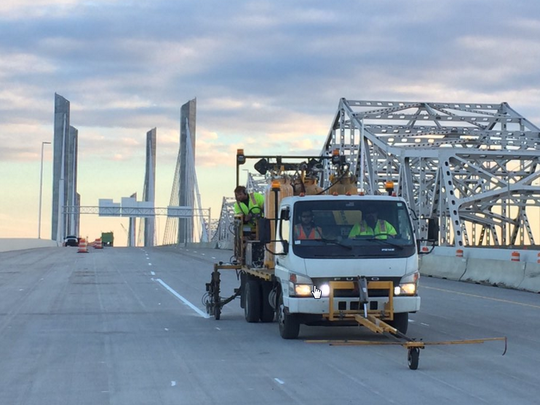Crews paint in lanes on the Abraham Lincoln Bridge, which opened to northbound traffic Sunday night. The bridge was originally expected to open Monday morning.