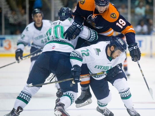 Florida Everblades' Corey Syvret (20) and Mike Ferrantino (22) check Greenville's Brandon Alderson (19) high in the air in the second period of action at Germain Arena Friday, October 14, 2016 in Estero.