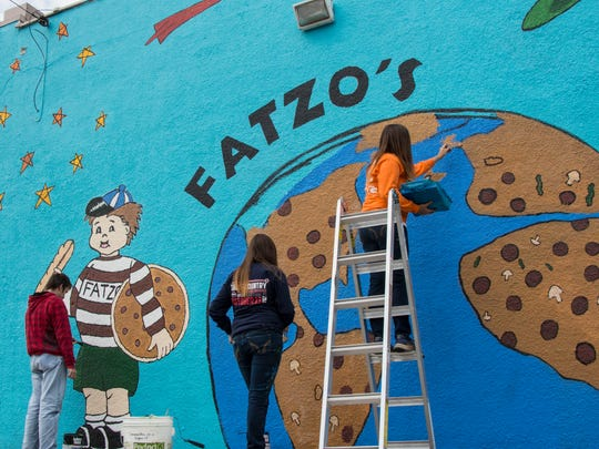Putting the finishing touches on a mural at Fatzo's Subs and Pizza in Manitowoc are, from left, Silver Lake College art students Randy Gruenweller, Amber Kiel and Erin Kiel.
