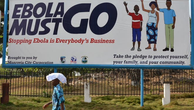 "A man walks past an ebola campaign banner with the new slogan ""Ebola Must GO"" in Monrovia."