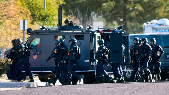 A Phoenix SWAT team enters a house at 28th St. and Acoma in search of the gunman who opened fire in an office building at 16th St. and Glendale, Wednesday, 1-30-2013.  Law-enforcement agencies in all 15 Arizona counties have obtained surplus gear from the Pentagon's 1033 program, as allowed under the National Defense Authorization Act of 1997.