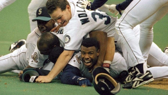 In this Oct. 8, 1995, file photo, Seattle Mariners' Ken Griffey Jr. smiles from beneath a pile of teammates who mobbed him after he scored the winning run in the bottom of the 11th inning of a baseball game against the New York Yankees in Seattle. The transcendent, once-in-a-generation athlete belonged to a little pocket of the country that never had the experience of the best athlete in their respective sport be theirs. And it's why when Griffey is all but certain to be announced as a Baseball Hall of Fame inductee next week, he'll take the entire Northwest with him to Cooperstown.