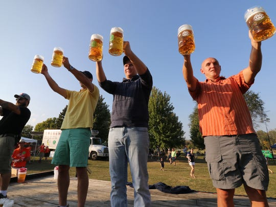 Competitors line up and hoist full litres of beer in a round of Masskrugstemmen, a German endurance game, during last year's Elm Grove Oktoberfest.