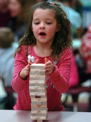 Harper Marsh, 6, removes a block from the Jenga structure.