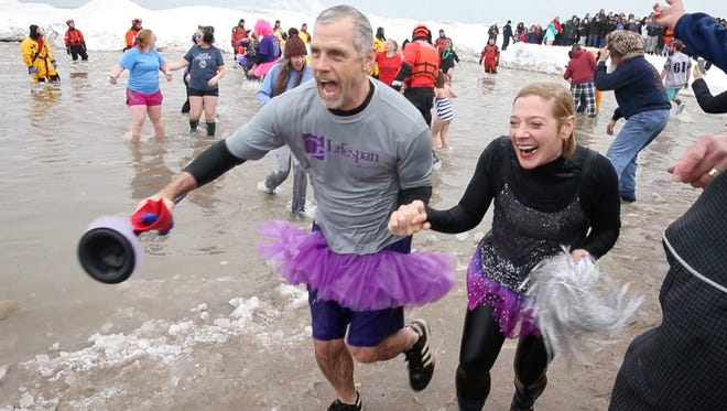 Plungers race back towards shore after taking a dip in frigid Lake Ontario at the 18th Annual Rochester Polar Plunge to benefit Special Olympics New York held at Ontario Beach Park in Charlotte Sunday, Feb. 11, 2018.
