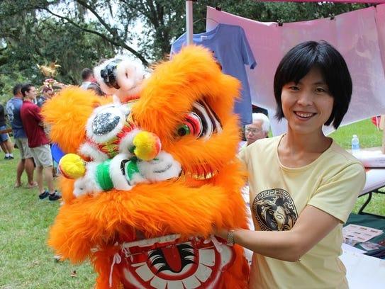 A woman strikes a pose alongside a dragon puppet at