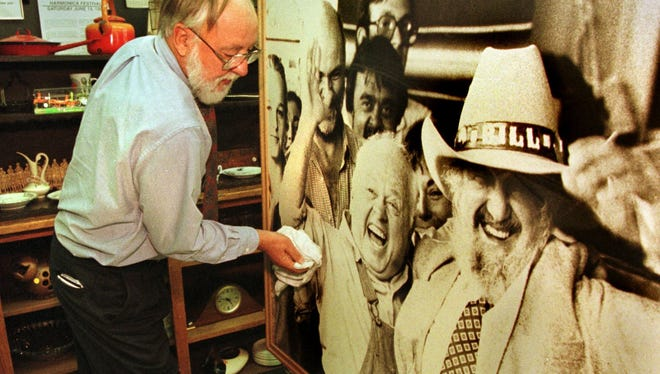 In this 1998 file photo, Tom Walz dusts off a photo of the late Bill Sackter, right, and actor Mickey Rooney displayed in Wild Bill's Coffee Shop at the University of Iowa School of Social Work.