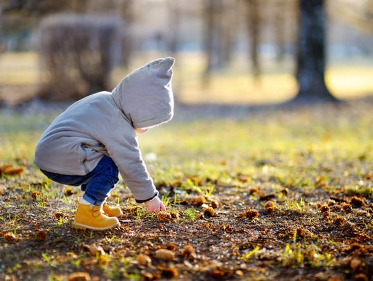 Toddler walking outdoors at the warm spring day