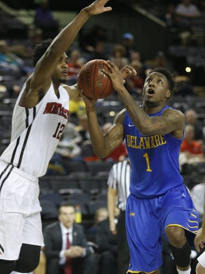 Delaware's Kory Holden drives on Northeastern's Quincy Ford in the first half of a CAA tournament quarterfinal at the Royal Farms Arena in Baltimore in 2015.