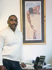 Robert L. Simpson, chief executive officer for Crispus Attucks Association in York, stands beside a painting he keeps over his desk. It reminds him to reach down to those least fortunate, he said.