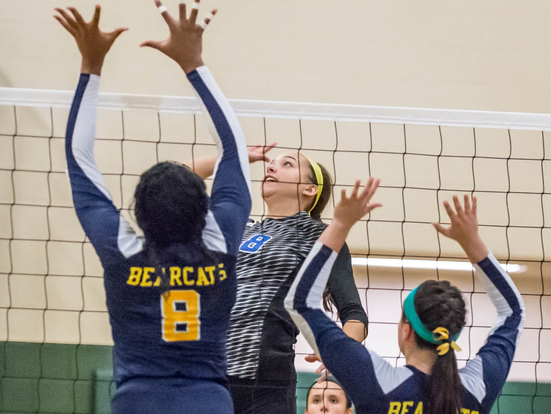 Harper Creek's Charley Andrews (8) goes for the point over the Bearcat's Jamesha Smith (8) and Mya Trevino (5) at the All-city volleyball tourney on Saturday.