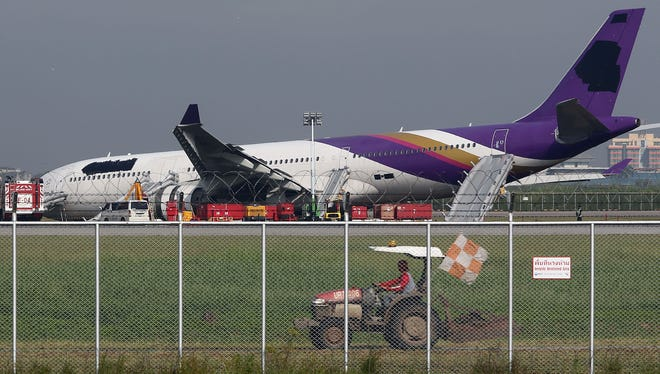 An airport worker drives a cart past a damaged Thai Airways Airbus A330-300 at Suvarnabhumi International Airport in Bangkok, Thailand, on Sept. 9, 2013.