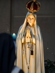 People pray the rosary with the Our Lady of Fatima