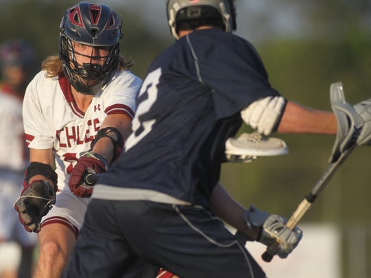Chiles defenseman Nic McEwey pokes his long stick at Maclay's Sam Chase.