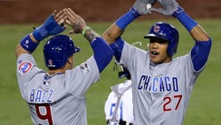 Addison Russell celebrates with Javier Baez after hitting