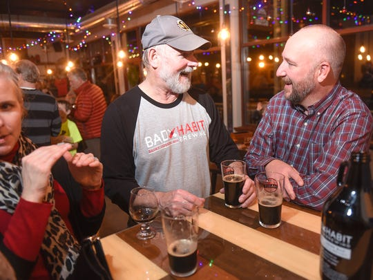 Homebrewer John Ludwig talks with friends during a