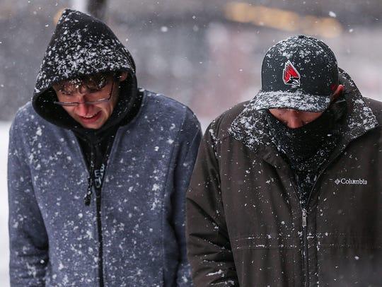 Pedestrians trudge through heavy snowfall in Downtown
