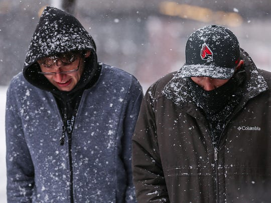 Pedestrians trudge through heavy snowfall in Downtown Indianapolis on March 24, 2018.