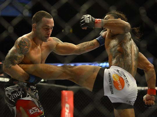 Frankie Edgar strikes Benson Henderson while holding his leg in their controversial UFC 150 bout.