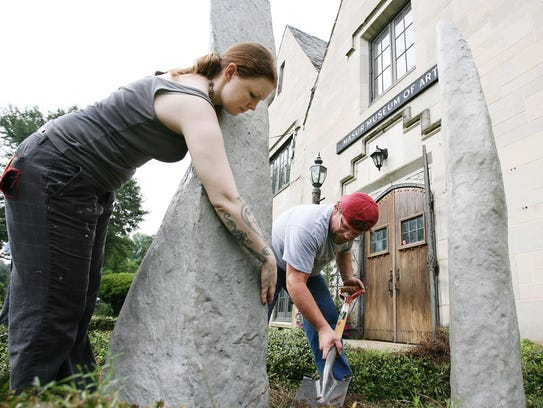 Artists set up a sculpture outside the entrance of