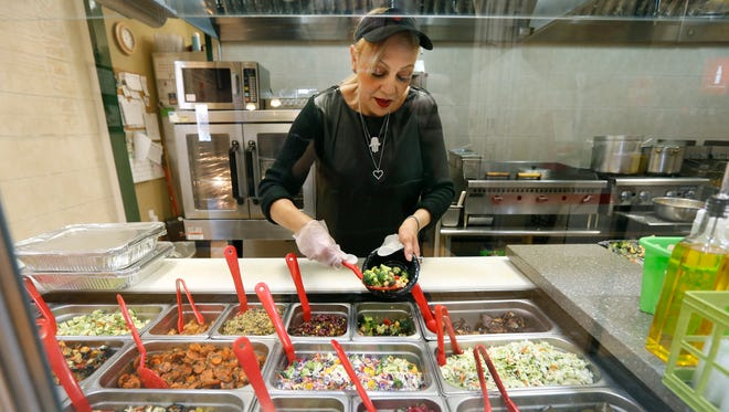 Ruth Cohen, chef and owner of Sabra Grill in Brighton, puts together orders.