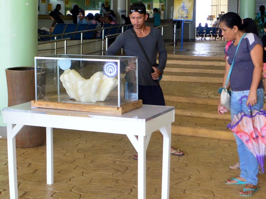 In this photo provided by Puerto Princesa Tourism Office, shows residents look at the giant pearl measuring 30cm wide (1ft), 67cm long (2.2ft) and weighing 34kg (75lb) on display in the lobby of the Puerto Princesa City Hall in Puerto Princesa city, Palawan province in southwestern Philippines Thursday, Aug. 25, 2016. Puerto Princesa Tourism Officer Aileen Amurao said the giant pearl was found by a relative fisherman ten years ago and entrusted to her for safekeeping and eventually to the mayor of the city. The still-to-be-authenticated find is said to be the largest in the world and would likely be valued in excess of US$100 million.