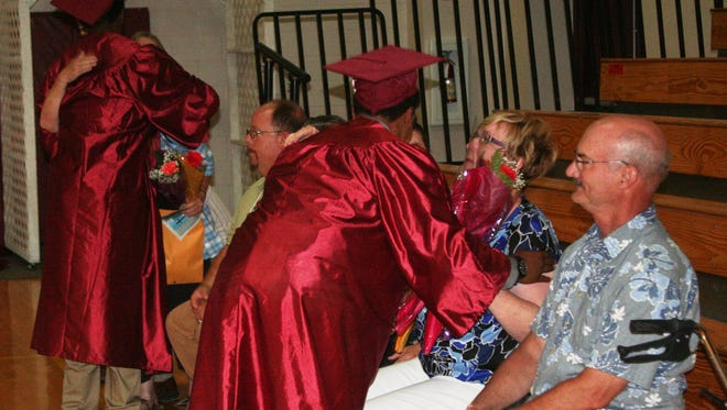 Rite of Passage-Silver State Academy graduates present flowers and give hugs to teachers and staff who have helped them during the Silver State Academy graduation in July.