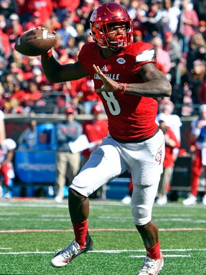 Louisville Cardinals quarterback Lamar Jackson (8) looks to pass against the North Carolina State Wolfpack during the second half at Papa John's Cardinal Stadium. Louisville defeated North Carolina State 54-13.
