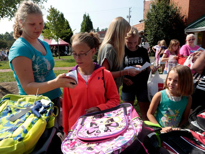Hailey Wickniff, Haylee Wetzel, and Madkynn Chandler pick out new backpacks at Rally in the Alley. The event offered Newark students a chance to sign up for youth development and engagement programs while giving out free backpacks, school supplies and uniforms.