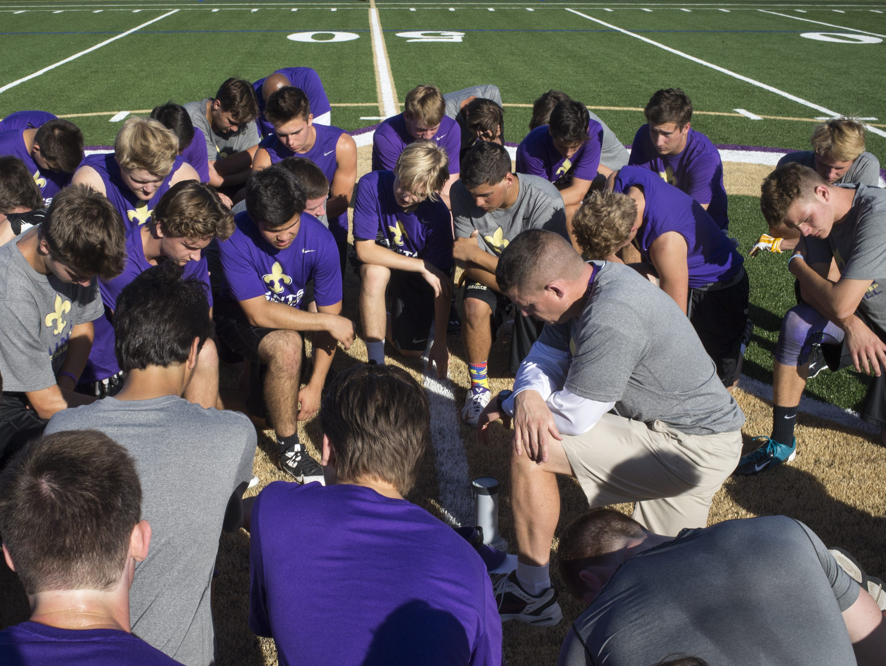 Notre Dame Preparatory High School football coach Mark Nolan prays with his team, May 28, 2015, after practice at Scot Bemis Field, 9701 E. Bell Road, Scottsdale.