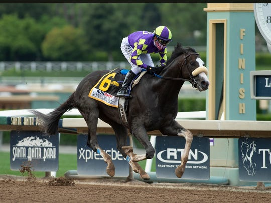 In a photo provided by Benoit Photo, C R K Stable's Honor A.P. and jockey Mike Smith win the Grade I $400,000 RUNHAPPY Santa Anita Derby Saturday, June 6, 2020 at Santa Anita Park in Arcadia, Calif.(Benoit Photo via AP)