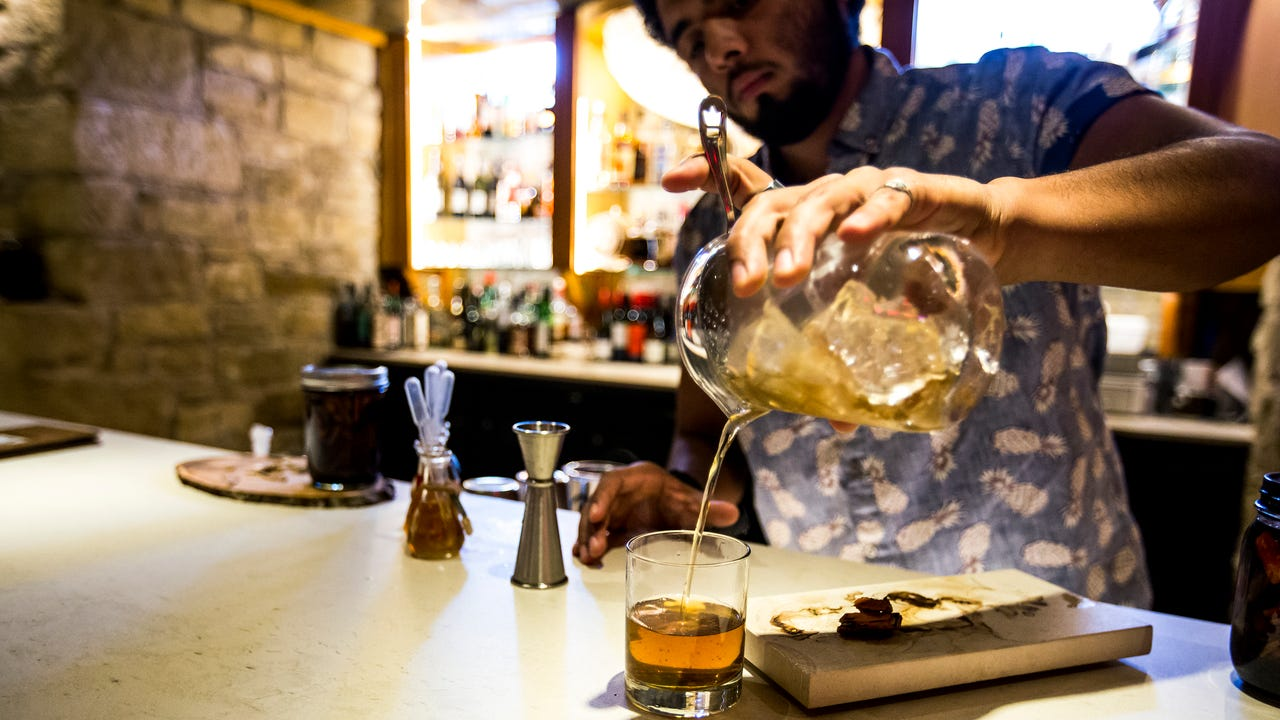 Jeffrey Oseguera, a bartender at La Cave in La Crosse, Wis., explains the bar's take on a classic old fashioned cocktail on Friday, September 22, 2017.