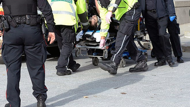 Paramedics and police wheel away a shooting victim at the National War Memorial near Parliament Hill in Ottawa Wednesday Oct. 22, 2014. A soldier standing guard at the National War Memorial was shot by an unknown gunman and people reported hearing gunfire inside the halls of Parliament. Prime Minister Stephen Harper was rushed away from Parliament Hill to an undisclosed location, according to officials.