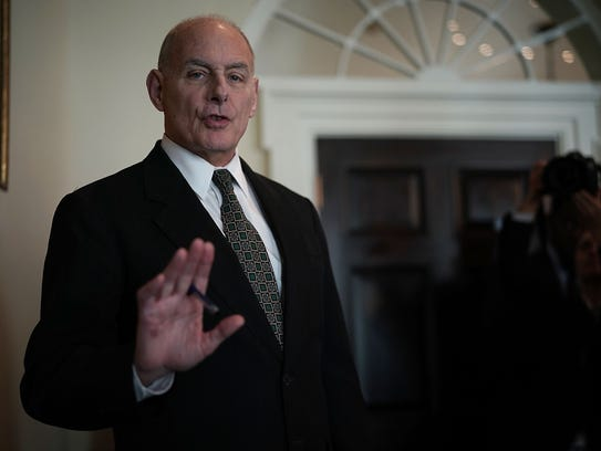 White House Chief of Staff John Kelly signals photographers