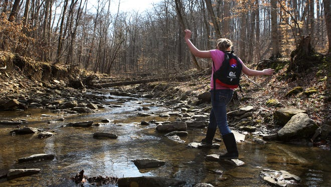 Lauren Higgins crosses a creek at the Cincinnati Nature Center, while on a five-mile hike with the Outdoor Adventure Club in Milford Saturday, March 21.