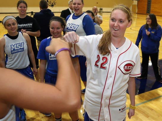 Lauren Hill gets congratulation from a teammate after practicing with her NCAA college basketball team at Mount St. Joseph University in Cincinnati on Thursday, Oct. 23, 2014. She's got only a few months to live, and she's spending a good part of it on the basketball court getting ready for her one shining moment. (AP Photo/Tom Uhlman)