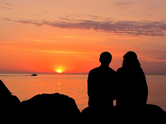 """""""The sun was setting over Lake Michigan near Holland when I noticed the couple in the photo,"""" said Phillip DePetro of Holland.  """"I took the silhouette shot, the sunset as a backlight.  I imagine this is a story in the lives of many couples in Michigan -- romantic evenings watching sunsets on the shores of a beautiful lake."""""""
