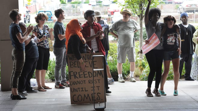Protestors demonstrate outside the Omni during the afternoon session  of the Governor's meeting on Saturday July 12, 2014, in Nashville.