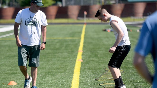Head coach Jeff Lindesmith works with a player as Central Catholic High School football workouts begin, Monday, June 01, 2020.