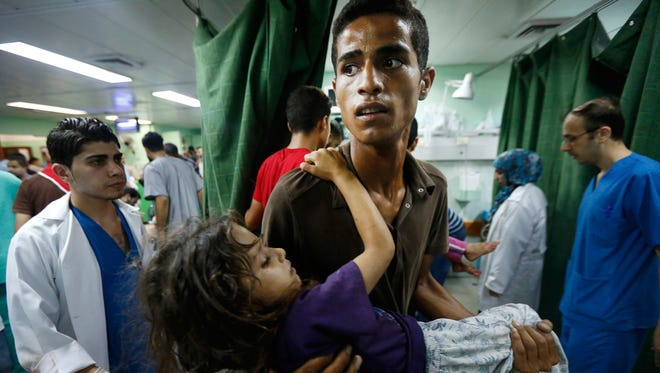 A Palestinian youth carries a child, wounded in an Israeli strike on a compound housing a U.N. school in Beit Hanoun, in the northern Gaza Strip, into the emergency room of the Kamal Adwan hospital in Beit Lahiya, Thursday, July 24, 2014. Israeli tank shells hit the compound, killing more than a dozen people and wounding dozens more who were seeking shelter from fierce clashes on the streets outside. Gaza health official Ashraf al-Kidra says the dead and injured in the school compound were among hundreds of people seeking shelter from heavy fighting in the area.