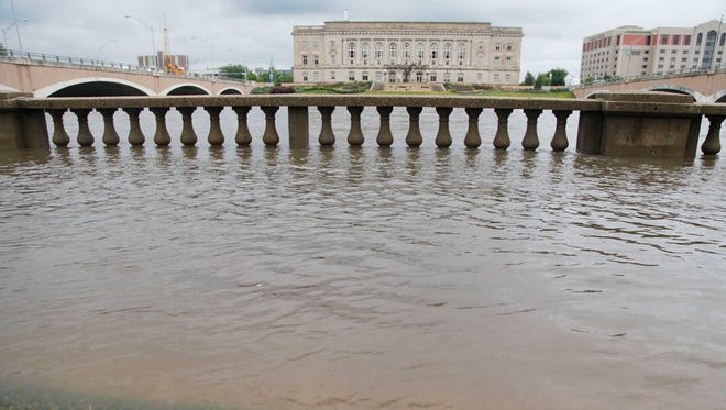 Minor flooding is occurring on the Des Moines River in downtown on Friday morning, June 27, 2014. When the river is at 25 feet it covers the walking paths along the river and surrounds the base of the Simon Estes Amphitheatre.