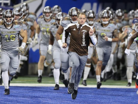 Western Michigan coach P.J. Fleck leads his team onto