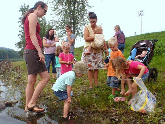 Parents and children learn about tadpoles  during a hike along the Chemung River.