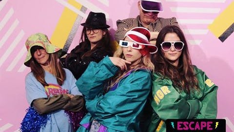 Carly Mallenbaum, the reporter in black, poses with her family at an '80s-themed escape room in a photo shared on Instagram in 2016.