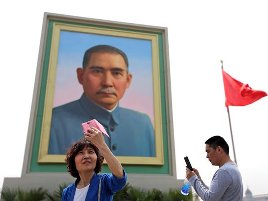 A woman uses a smartphone to take a selfie in front of a portrait of Sun Yat-sen, widely regarded as the founding father of modern China, at Tiananmen Square in Beijing in 2015.