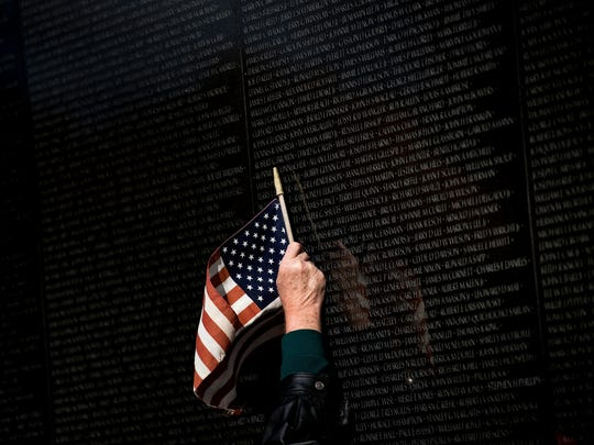 A man points to a name while visiting the Vietnam War Memorial on Veterans Day in Washington, D.C. Mission BBQ embraces the theme of patriotism and honoring those who served for our country.