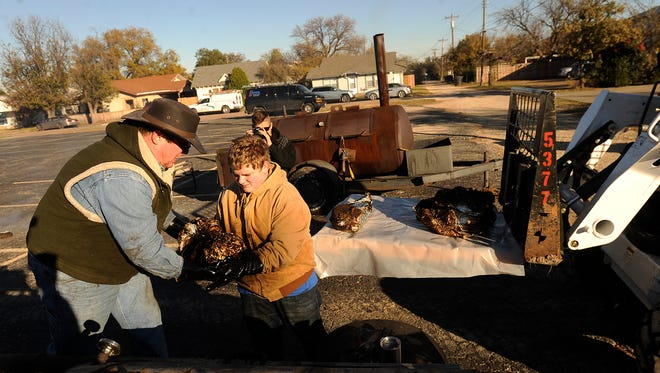 Dee Lott (left) hands a cooked brisket to Boy Scout Aaron Bailiff, 14, to cool during Troop 232's fundraiser on Saturday, Dec. 10, 2016.