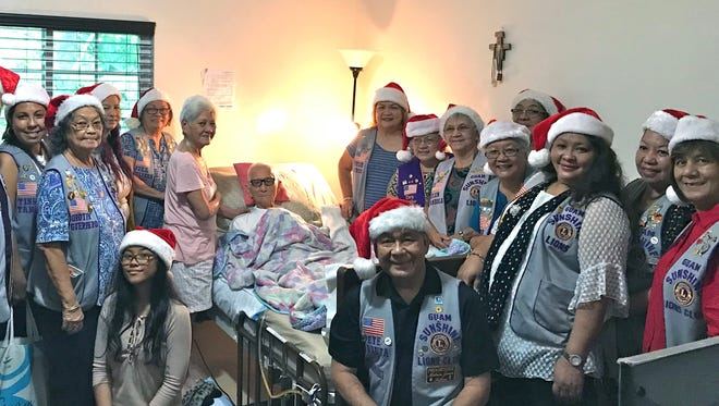 "Jose Reyes, 82, of Agat, was the recipient of a fruit basket, song, and cheer from members of the Guam Sunshine Lions Club, whose club project is ""Caring for the Sick and the Elderly,"" on Dec. 16. Pictured in pink: Frances, his wife with members of the Guam Sunshine Lions Club."