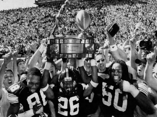 Iowa players, from left, Clinton Solomon, Jovon Johnson and Geroge Lewis carry the Cy-Hawk Trophy off the field after beating Iowa State, 17-10, Sept. 11, 2004, at Kinnick Stadium in Iowa City.